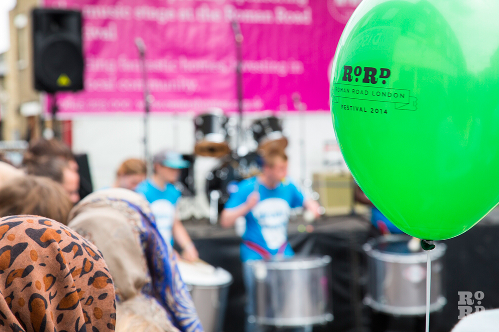 Drum works playing at Roman Road Festival with green festival balloon in foreground