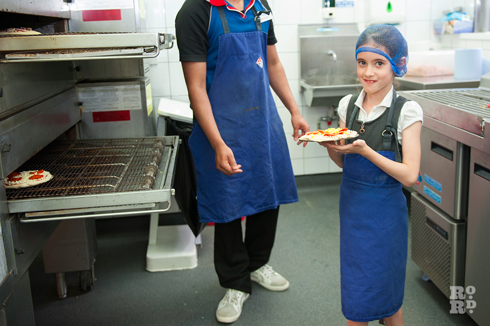 Young girl in blue hair net and blue apron in Domino Pizza kitchen holding her pizza creation and looking proud..