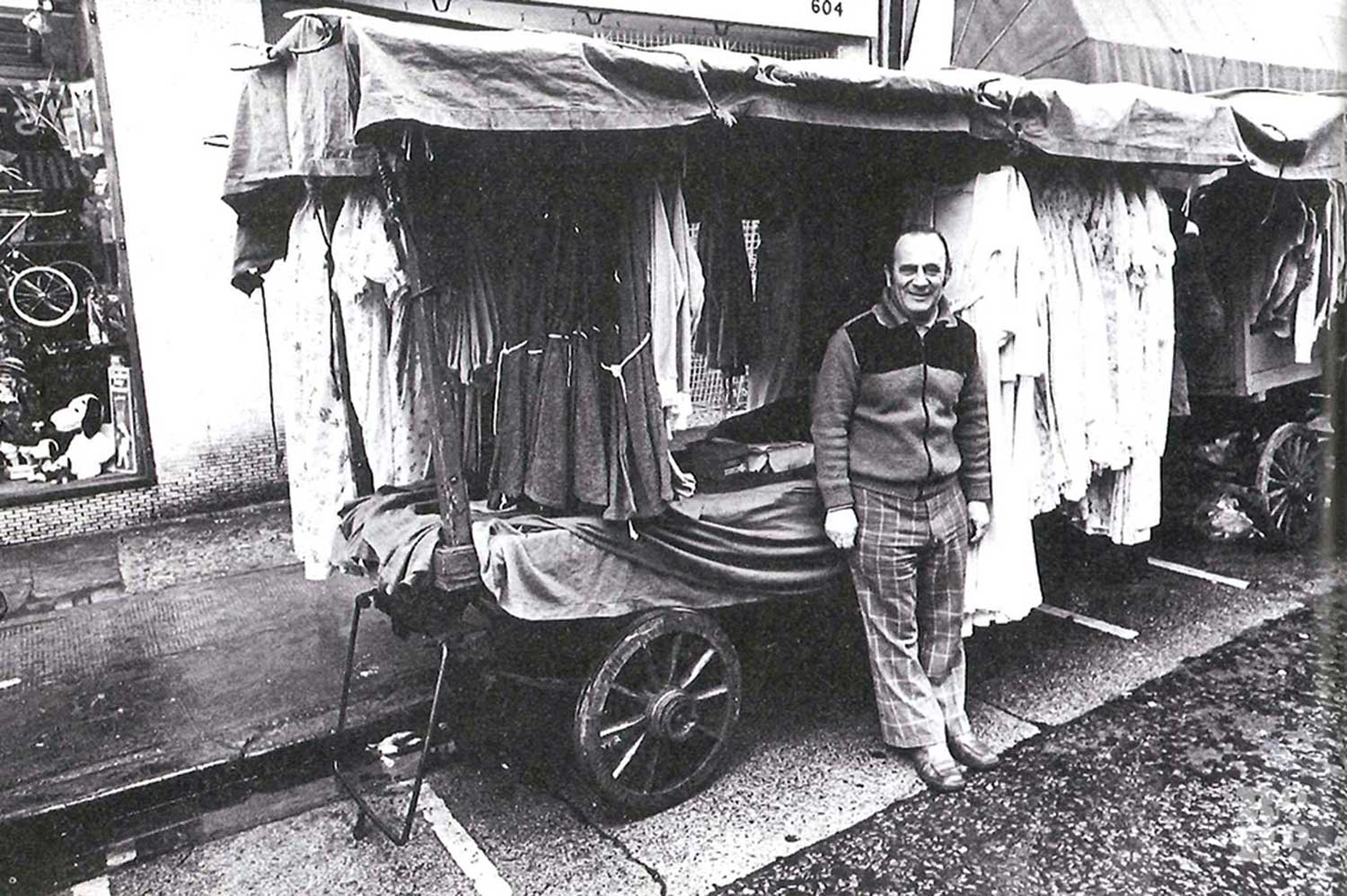 Roman Road Market trader Harry da Costa, wearing check trousers, at his stall in the 1970s