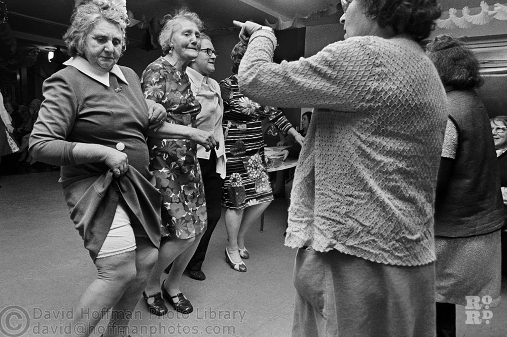 Elderly women dancing in community hall