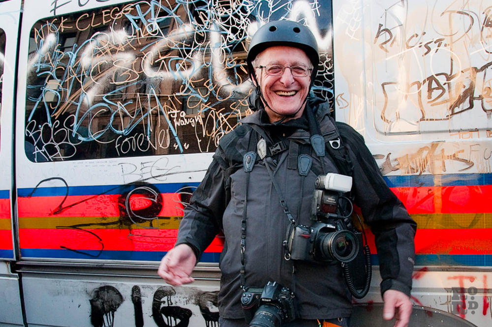 Photographer David Hoffman wearing protective helmet and bullet proof vest in front of a police riot van