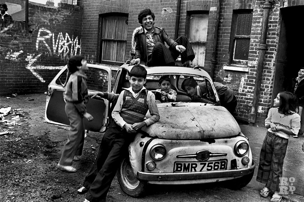 Group of Asian boys playing with car in East End slum, by David Hoffman