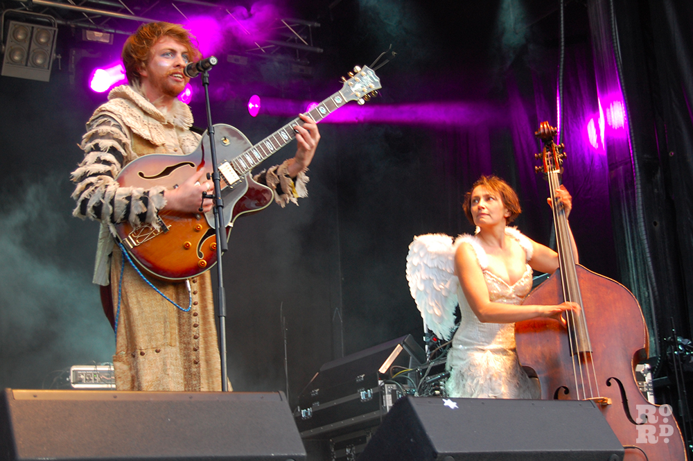 Rum Buffalo band members dressed as Elizabethan and angel playing cello and guitar live on stage