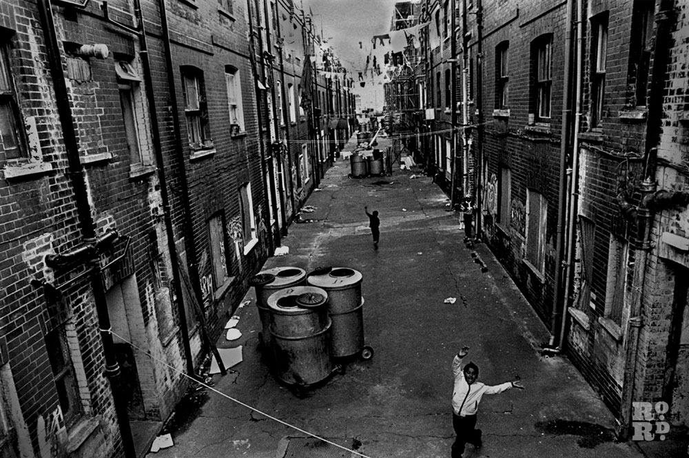 Black and white photo of Asian boy dancing in the streets, East End slums, by David Hoffman