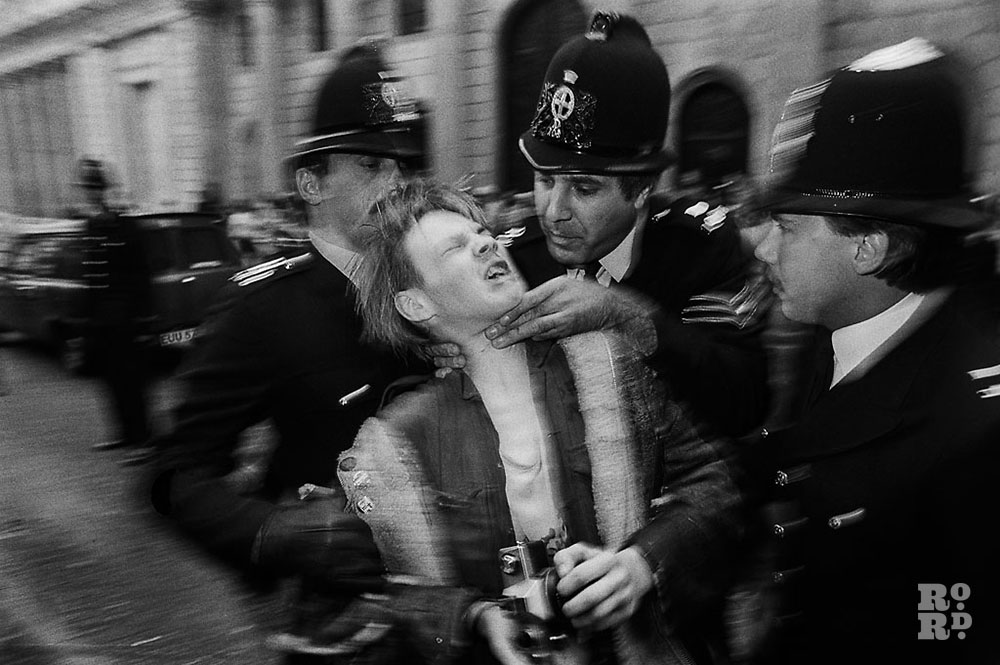 Black and white photograph of demonstrator being gripped around neck by police officer at G20 riots in London, by photographer David Hoffman