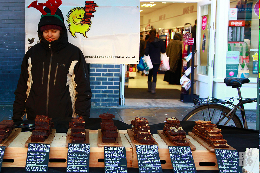 Woman in big coat and reindeer antlers hat, selling chocolate brownies at street food stall.