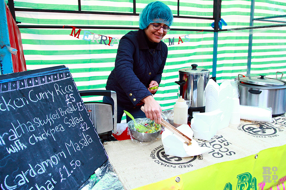 Woman in a hairnet selling Indian food at street food stall with Merry Christmas garland in felt multi-coloured lettering.