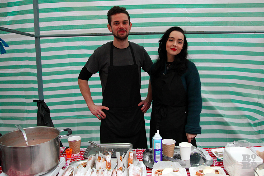 Young couple standing against green and white tarpaulin street food stall wearing black apron.