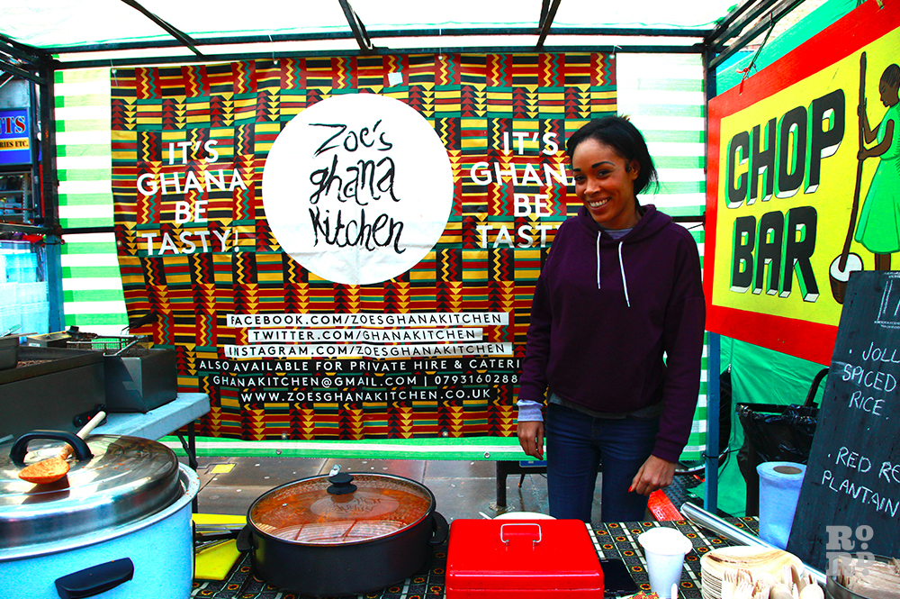 Street food stall with woman smiling and standing in front of African print fabric