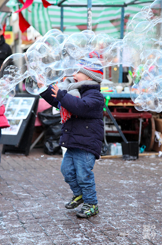 Boy laughing and trying to catch giant bubbles in outdoor street market.