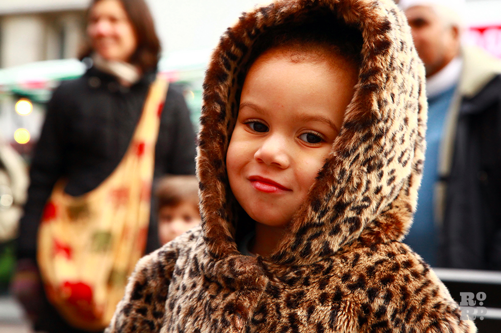 Child in hooded leopard print coat.