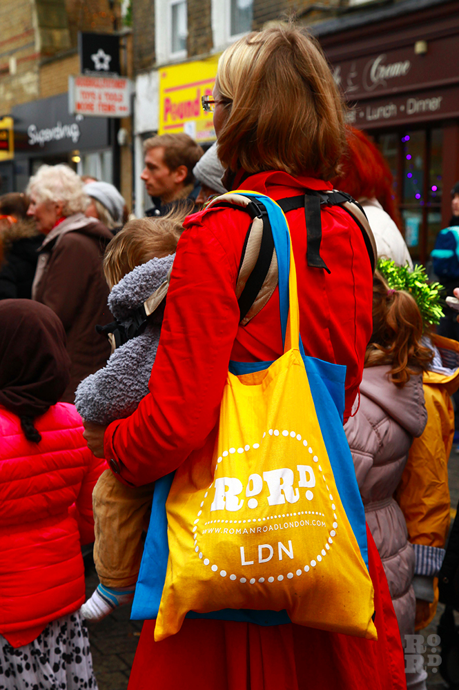 Woman in red coat with yellow and blue Roman Road LDN tote bags slung over shoulder.