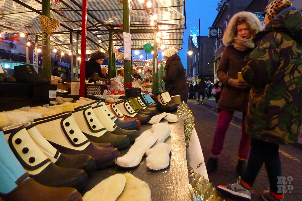 Market stall selling ankle wet weather boots, at dusk lit by festoon lighting.