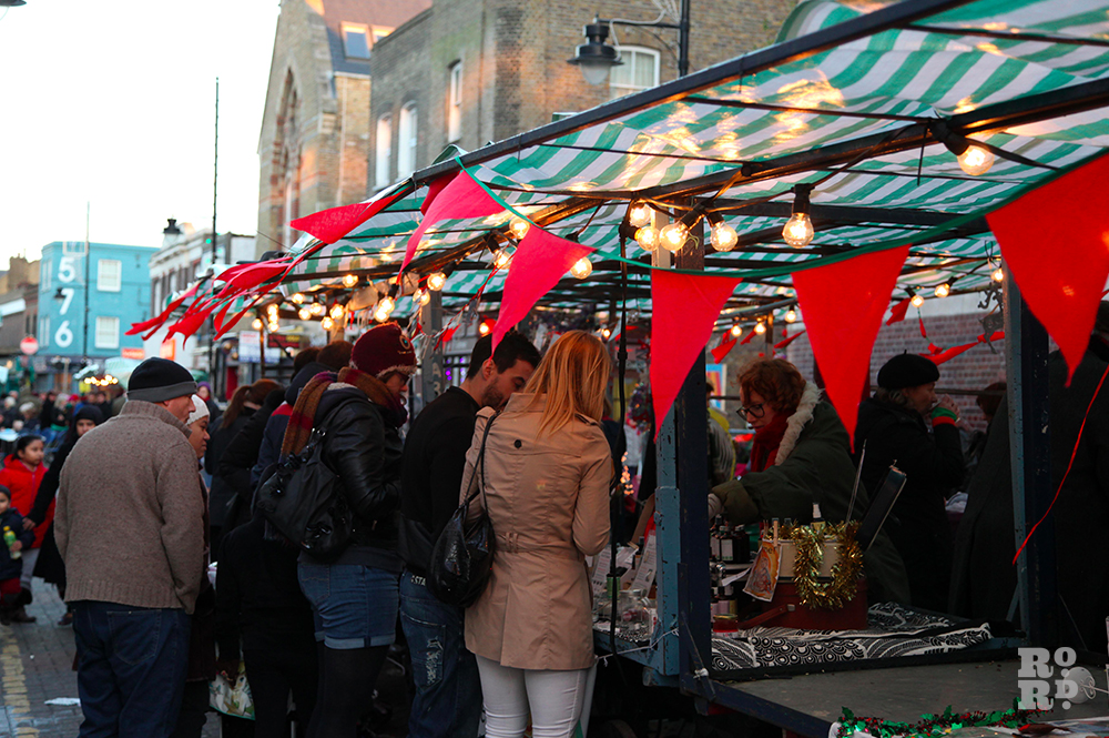 Red bunting flying in wind with festoon lighting on market stall with green and white tarp.
