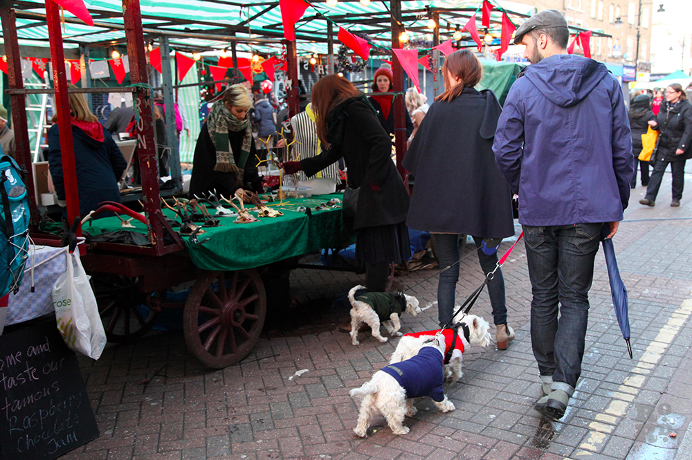 Man with small white dogs walking past market stalls