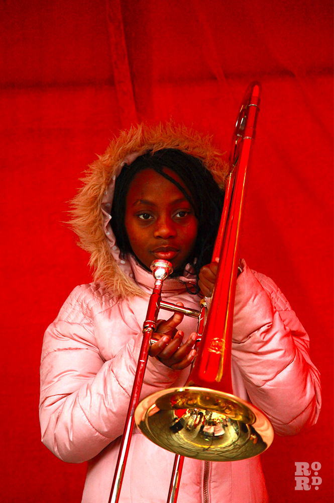 Afro-Caribbean girl in pink anorak with fur trim hood, playing trumpet against backdrop of red velvet.