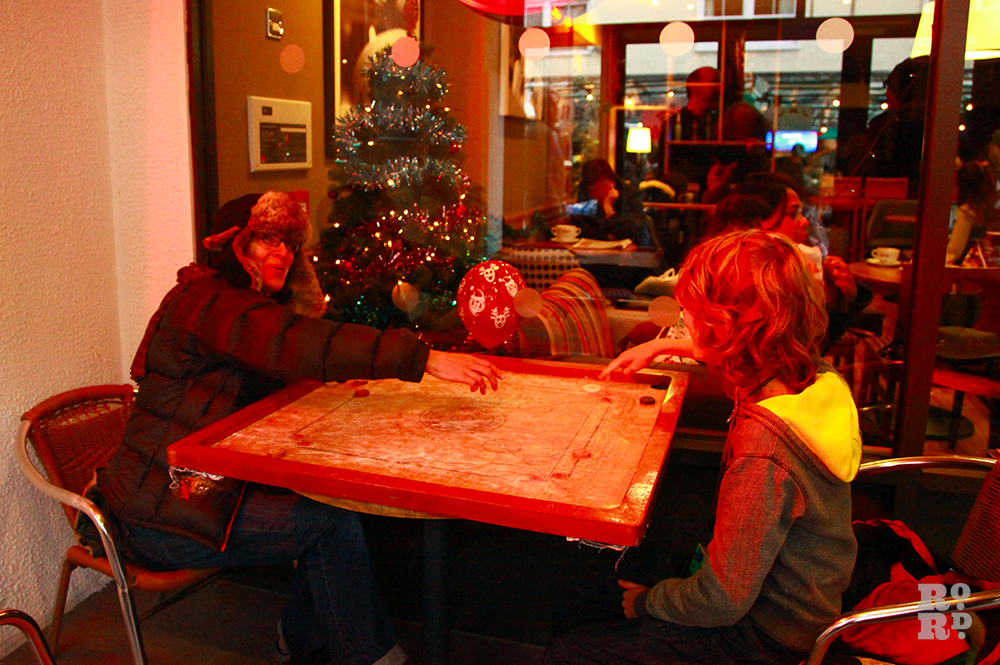 Woman and boy playing carrom outside a cafe on a cold day.