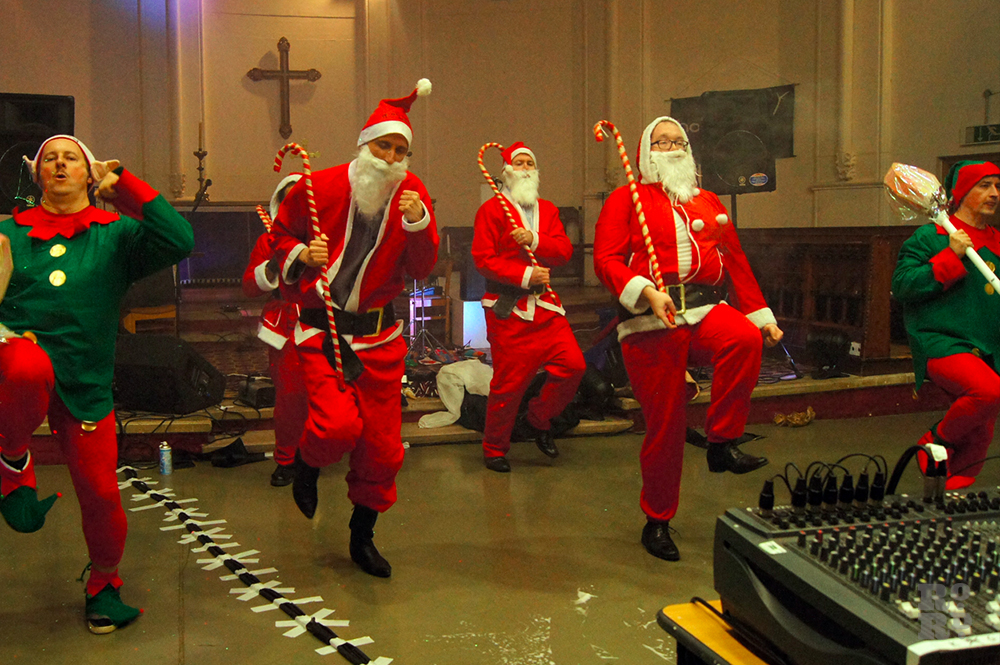 Dance troupe dressed as Father Christmas holding cane, performing in a church.