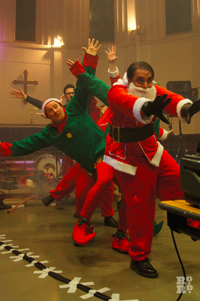 Cabaret dance featuring men dressed as father christmas and elves, performing in a church.