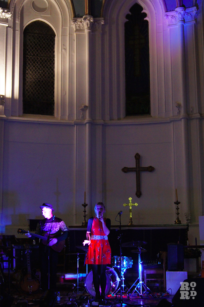 Girl in red dress singing on stage in Church, in front of large cross and tall windows.