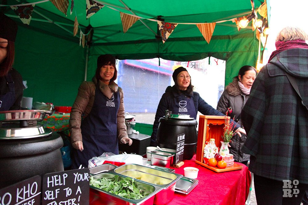 Laughing Vietnamese women selling street food from green gazebo with bunting.