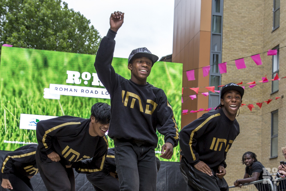 IMD Legion dancers performing in front of Roman Road outdoor screen