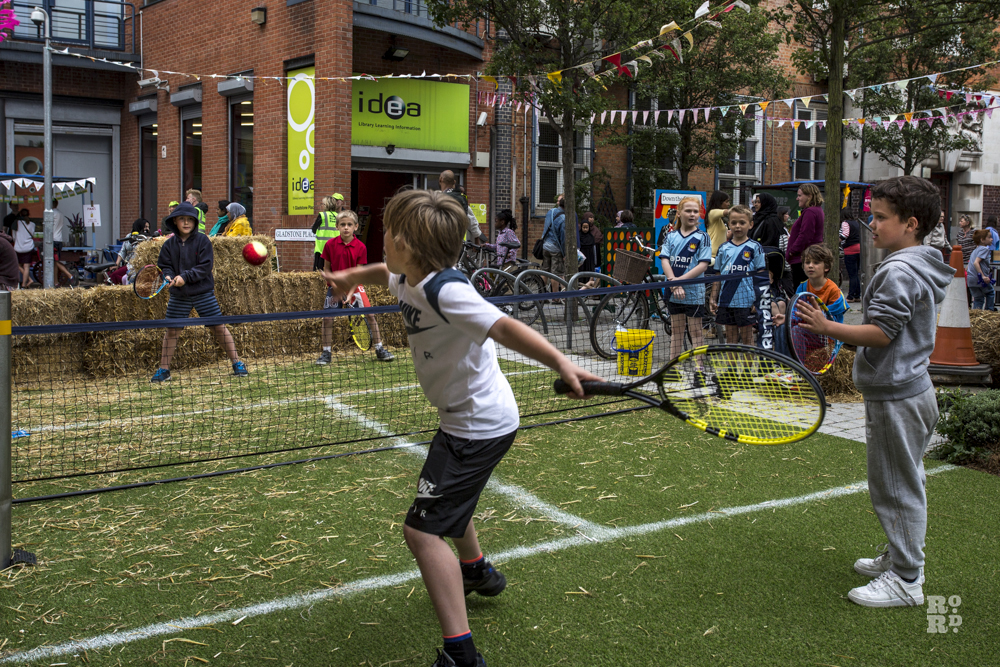 Children playing tennis on artificial lawn in urban setting