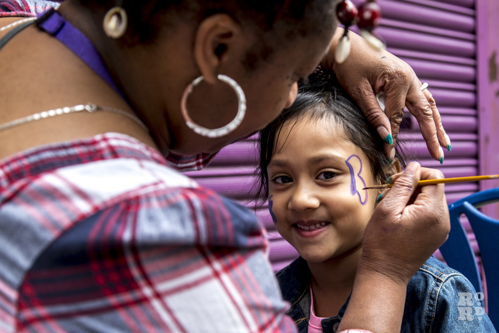 Black woman applying face paint to young asian girl at Roman Road Festival, London