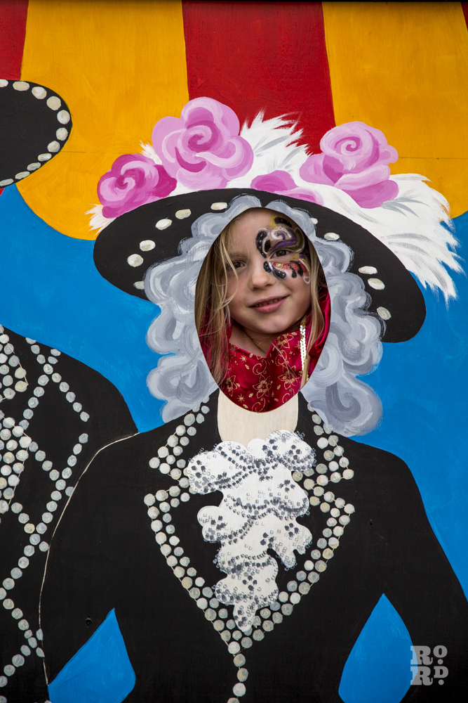 Young girl with face painted, Aunt Sally board East End style of Pearly Queen and Pearly King