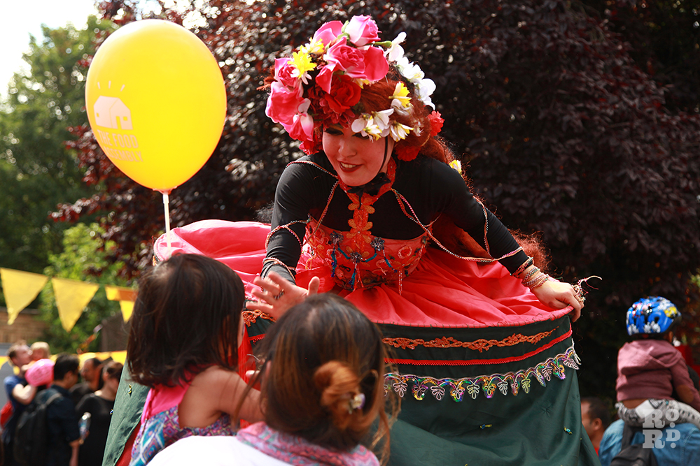 Ramanaya stilt walker talking to child with yellow balloon at Roman Road Festival