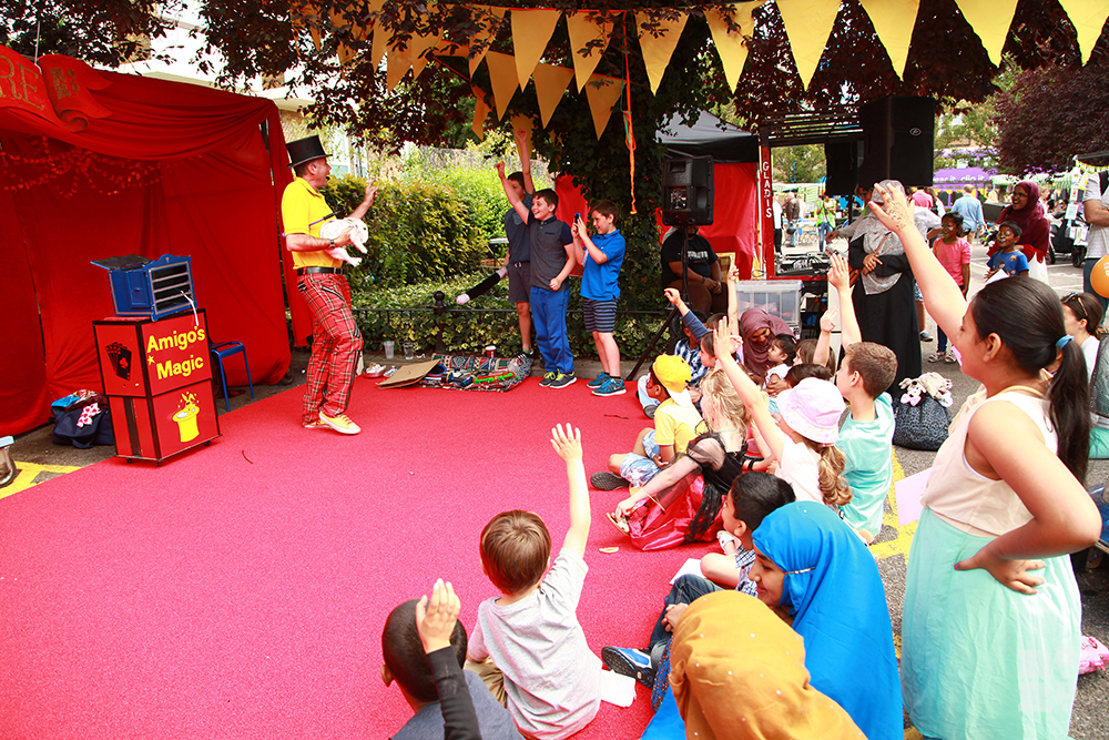 Magician on red carpet with children holding up hands, village fete bunting