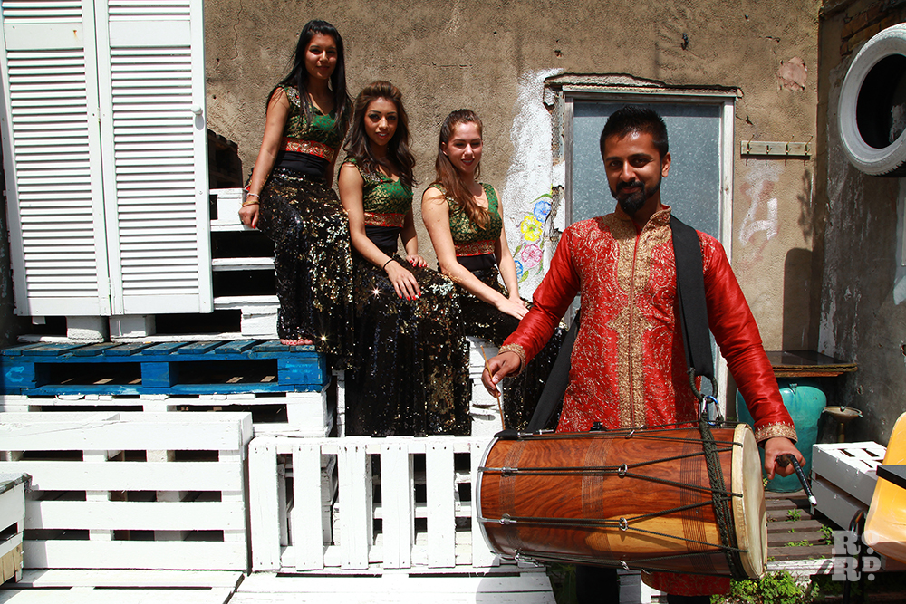 Bollywood dancers and drummer in courtyard
