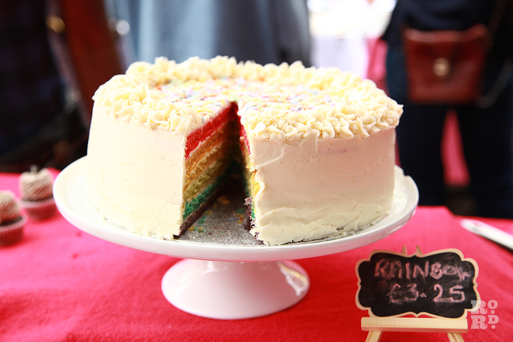 Cake on a stand with rainbow layers and butter icing