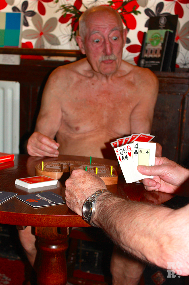 Two nude men playing cribbage in pub