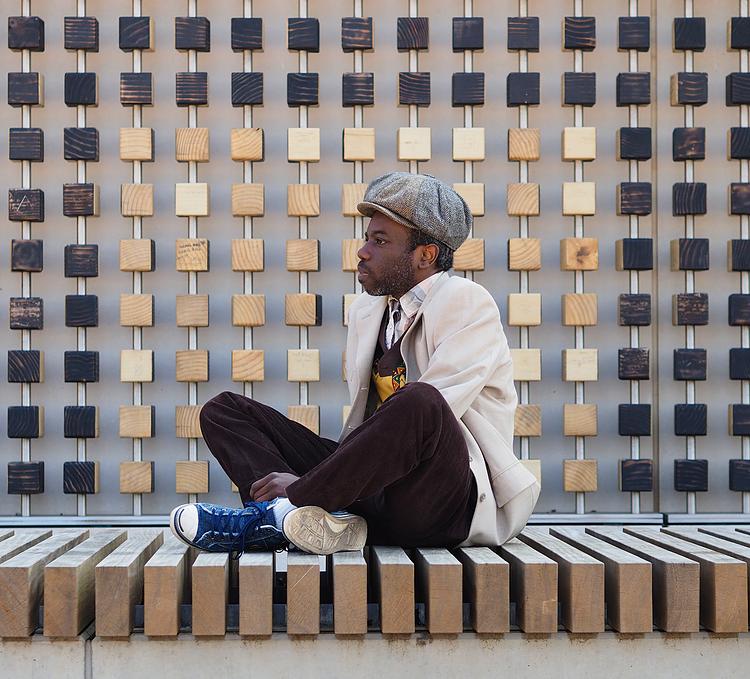 Munto Aldo musician sitting cross legged wearing cap and white jacket