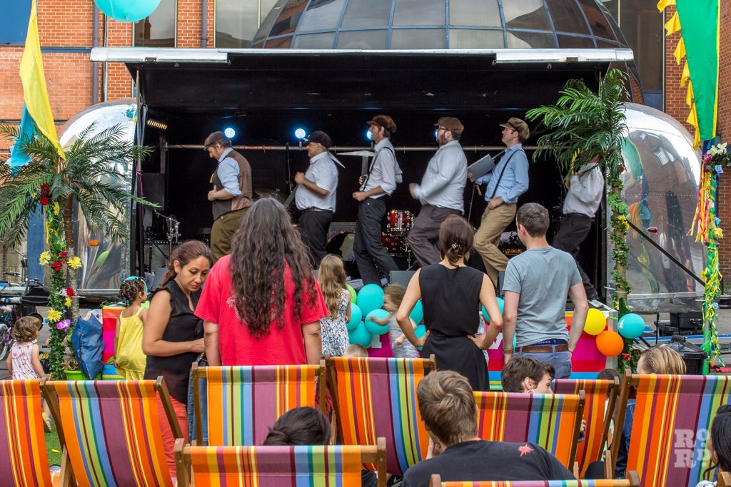 Psychedelic dance troop The Action Men on the Airstream stage at Roman Road Summer Festival, watched by audience seated in stripy deckchairs