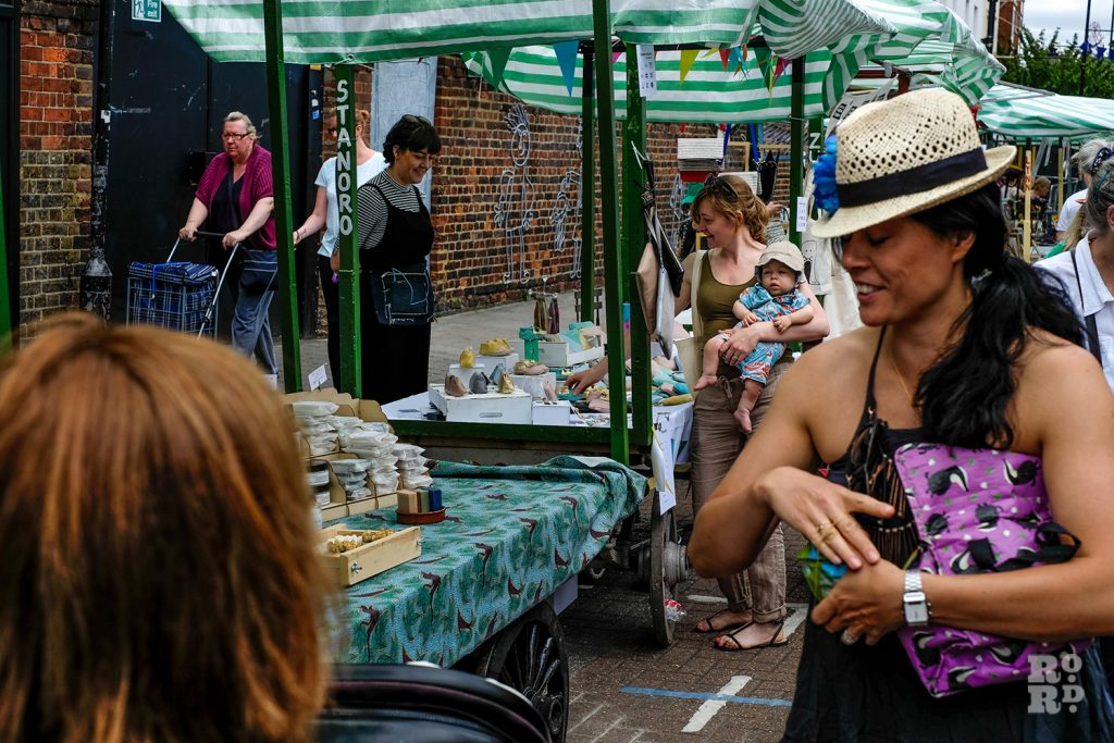 Women in straw hat enjoying Urban Makers East market at Roman Road Summer Festival 2016