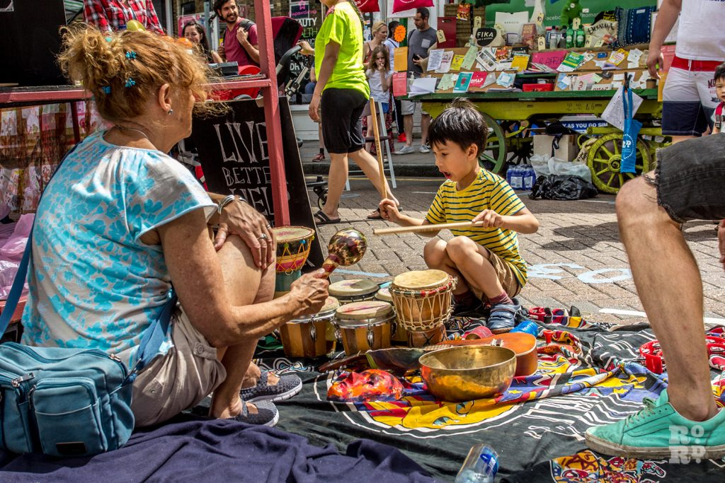 Young child playing tribal drums on the street at Roman Road Summer Festival