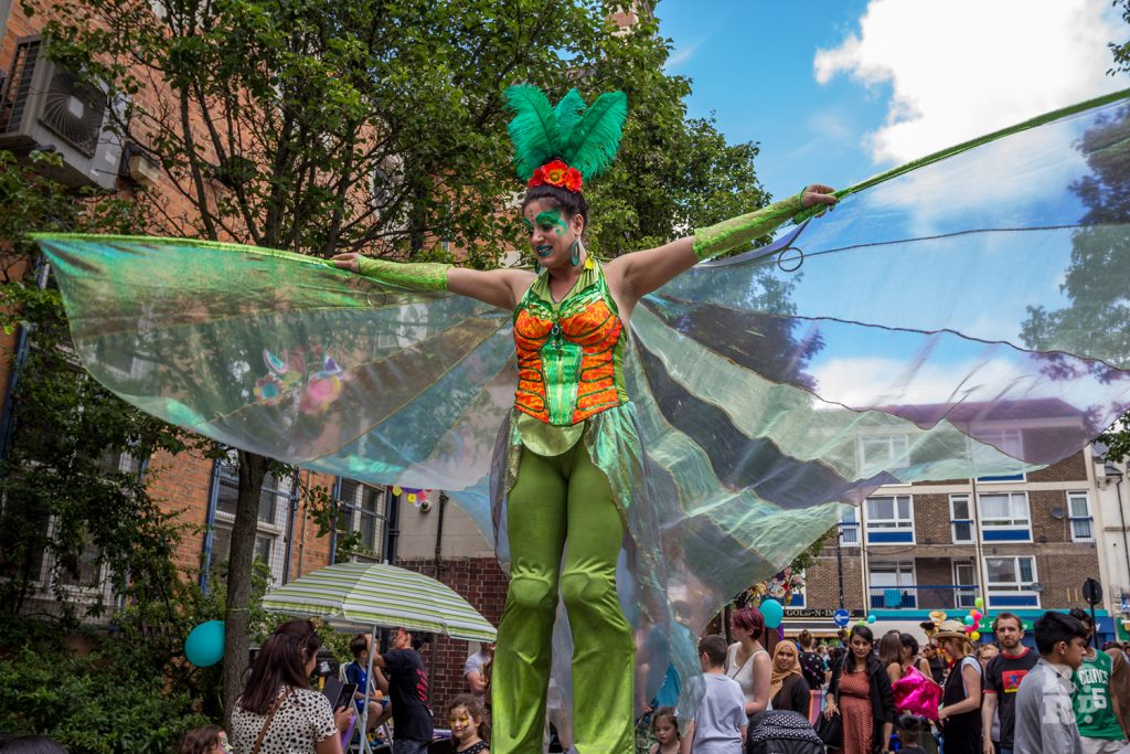 Slilt walker in green fairy outfit with wings spread at Roman Road Summer Festival 2016