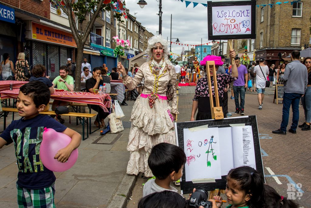 Performers in fancy dress bearing a placard saying Welcome to Roman Road at Roman Road Summer Festival 2016