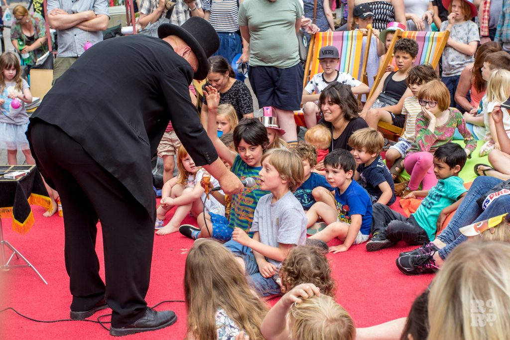 Magician entertaining children at Roman Road Summer Festival 2016