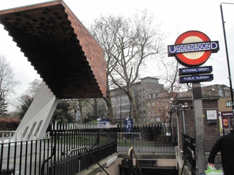 Memorial by stairs and tube sign