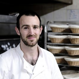 Miller the baker standing in front of over, smiling.
