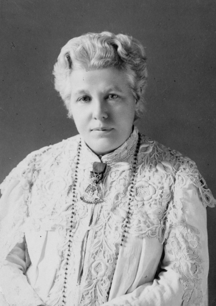 Annie Besant sitting, wearing a white blouse, in her old age.
