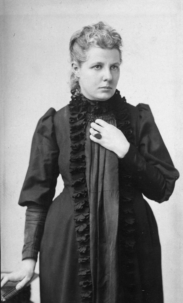Blakc and white photograph of Annie Besant in a black dress looking stately.