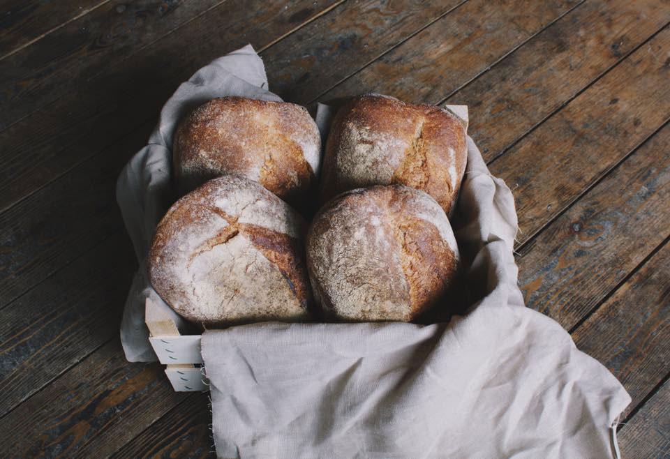 Four sourdough bread loaves in a basket