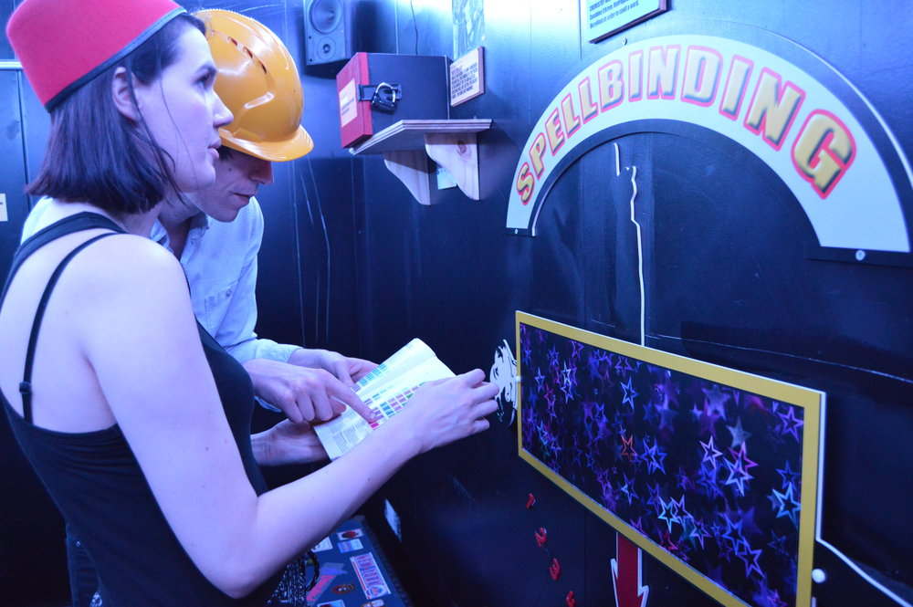 Man and woman wearing hard hats and playing a mystery escape game