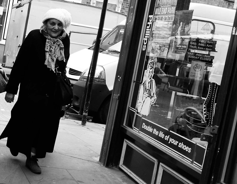 Woman in a wooly hat walks down Roman Road market