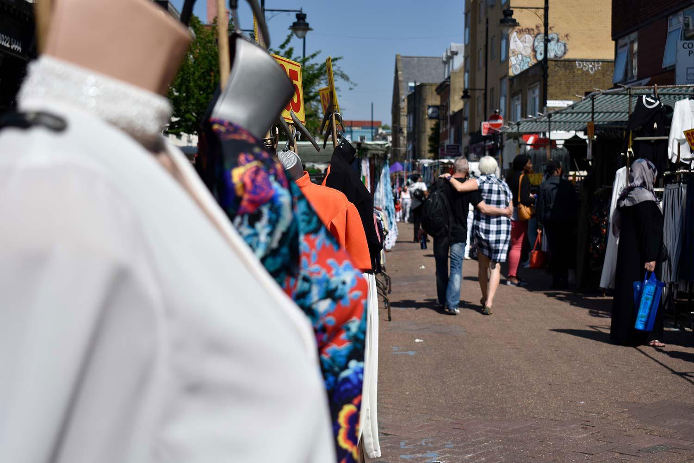 Couple walk arm-in-arm down Roman Road market
