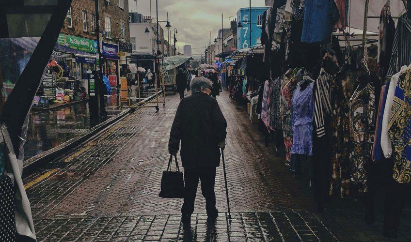 Woman walks down Roman Road Market